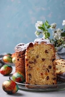 Paascake craffin en marmeren kleurrijke eieren op een lichtblauw oppervlak. concept van de lente orthodoxe kerkvakantie. verticaal formaat. detailopname
