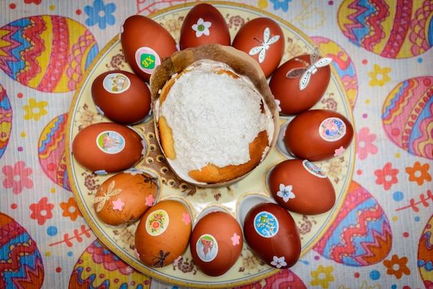 Paascake en versierde kippeneieren op een bord. paastraditie: kippeneieren worden uitgewisseld en ze zeggen:
