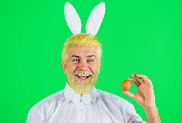 Paasdag, gelukkig bebaarde man met konijnenoren met paasei, eieren zoeken, konijnenman.