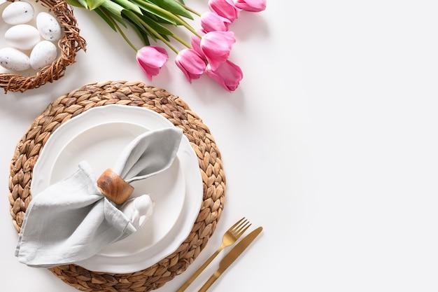 Paasdiner met eieren, feestelijk vaatwerk en tulpen op witte ondergrond