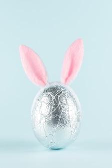 Paasei verpakt in een zilveren folie met roze konijnenoren tegen pastelblauwe achtergrond