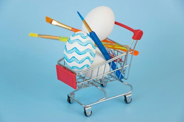 Paasei versierd in blauwe golven met andere witte eieren en kleurrijke verfborstels in winkelwagen op blauwe achtergrond.