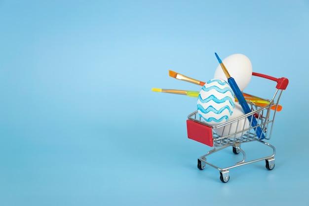 Paasei versierd in blauwe golven met andere witte eieren en verfborstels in winkelwagen op blauwe achtergrond.