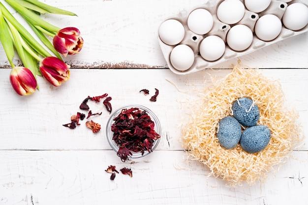 Paaseieren, beschilderd met natuurlijke kleurstoffen, hibiscusbloemen, karkadethee, op een witte verouderde houten tafel, rode lentebloemen tulpen.