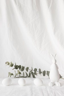 Paaseieren dichtbij installatietakjes en cijfer van konijn