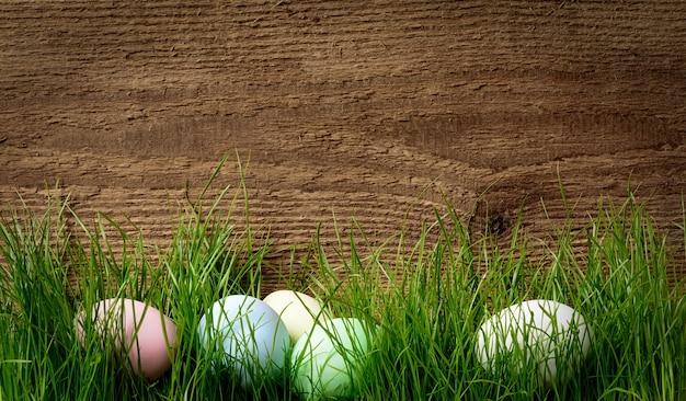 Paaseieren die in groen gras in de buurt van de bruine ruwe houten muur liggen, kopieer ruimte.