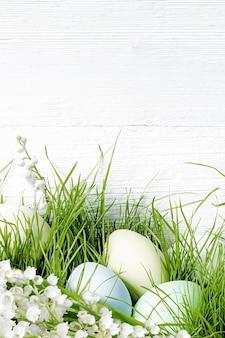 Paaseieren die in groen gras met lelietje-van-dalen bloemen leggen. paasdecoraties voor de feestdagen op witte houten achtergrond.