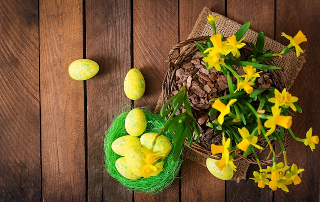 Paaseieren en bloemen op een donkere houten tafel. bovenaanzicht