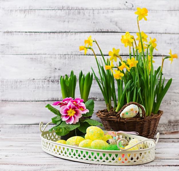 Paaseieren en bloemen op een lichte houten tafel