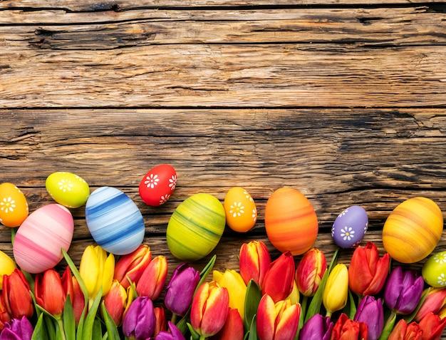 Paaseieren en tulpen op houten planken