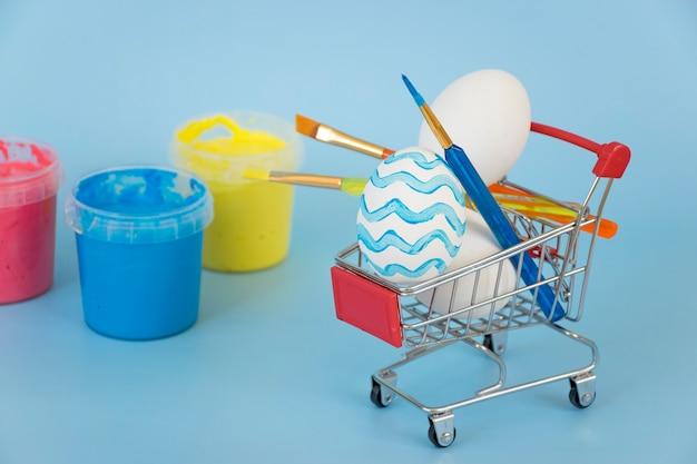 Paaseieren en verfborstels in winkelwagen met flessen met verf op blauwe achtergrond.
