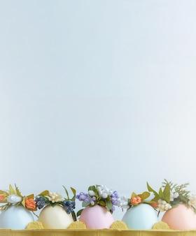 Paaseieren geschilderd in pastelkleuren in een eierrekje met kransen erop