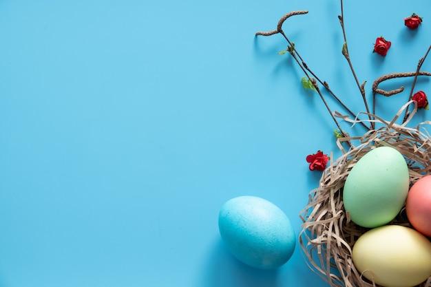 Paaseieren geschilderd in pastelkleuren met nest op blauwe ondergrond