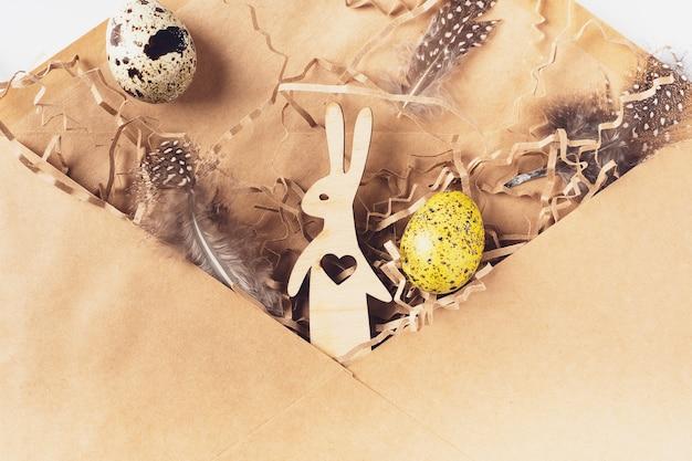Paaseieren, haas, veren, hooi in een ambachtelijke envelop op een witte achtergrond. vakantie bericht vrolijk pasen, correspondentie concept. plat lag, bovenaanzicht. paas kaart.