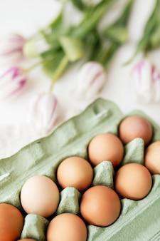 Paaseieren in een groene doos en tulpen flatlay