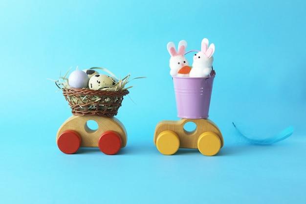 Paaseieren in een mand, decoraties en hazen op speelgoedauto's, gefeliciteerd, briefkaart