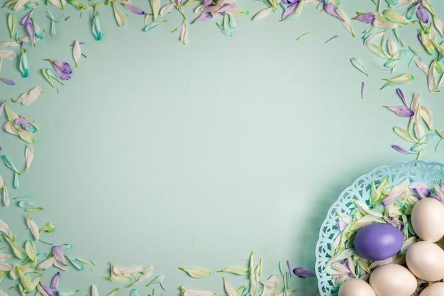 Paaseieren in een mand en kleurrijke bloemblaadjes van lentebloemen op een lichtgroene achtergrond.