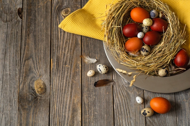 Paaseieren in een nest op een metalen plaat op een houten tafel. vrolijk pasen concept