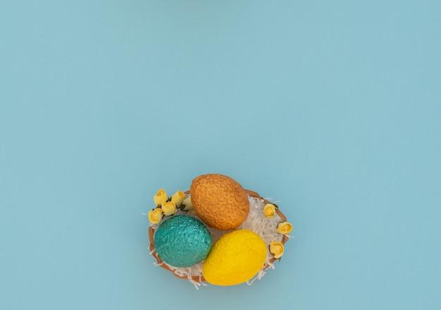 Paaseieren in eiermand met wit papier als een nest en gele lentebloemen op blauw