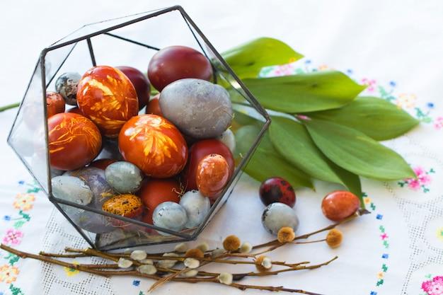 Paaseieren in glazen pot met groen bladeren. lente en bloeiende concept.