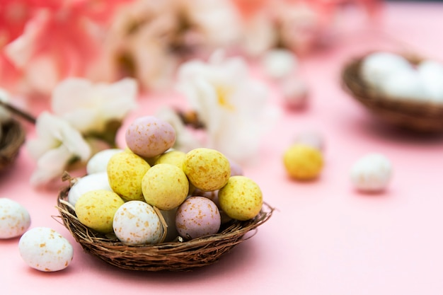 Paaseieren in het nest op roze achtergrond. lente wenskaart met kopie ruimte.