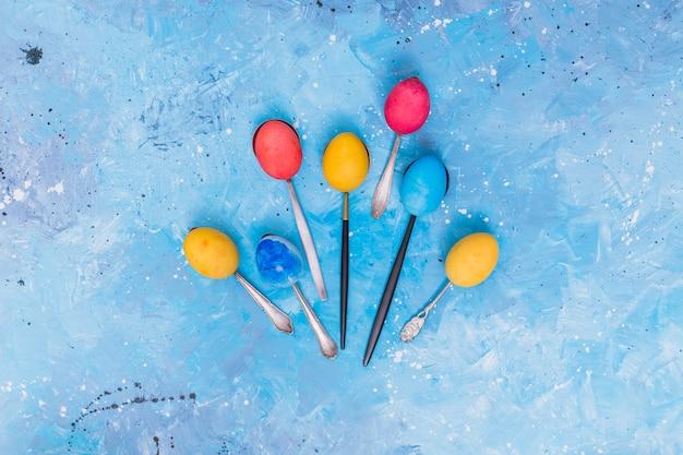 Paaseieren in lepels op blauwe lijst