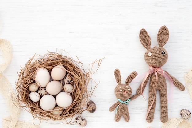 Paaseieren in nest en handgemaakte gehaakte konijnen op witte achtergrond. bovenaanzicht.
