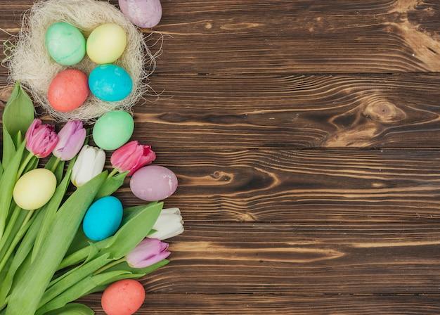 Paaseieren in nest met tulpen op tafel