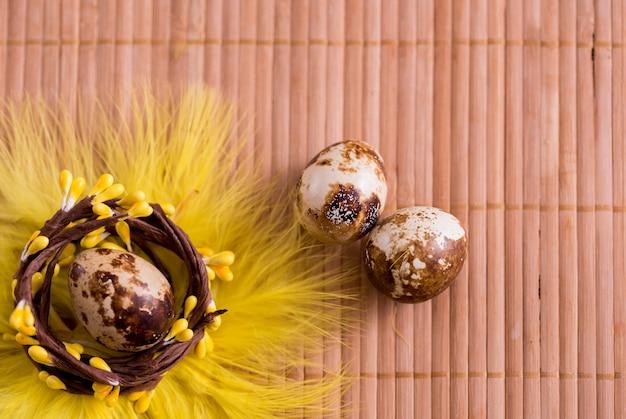 Paaseieren in nest op kleuren houten achtergrond