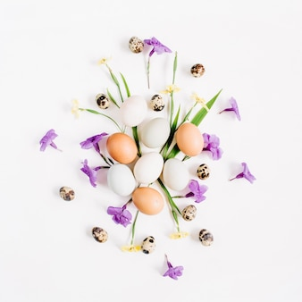 Paaseieren, kwarteleitjes, gele en paarse bloemen op een witte ondergrond