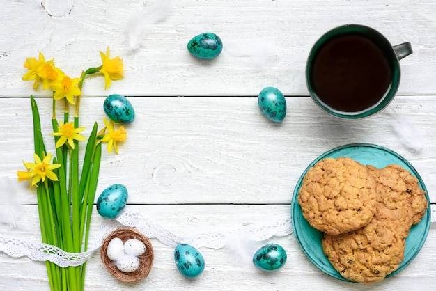 Paaseieren, lentebloemen, kopje koffie en koekjes voor het ontbijt