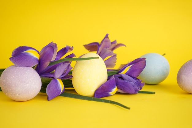 Paaseieren met bloemen op een gele achtergrond.