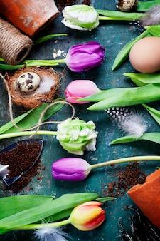 Paaseieren met lente tulp bloemen en tuingereedschap op vintage houten bord