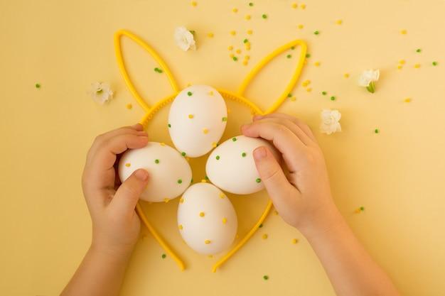 Paaseieren met stippen in de handen van een kind.