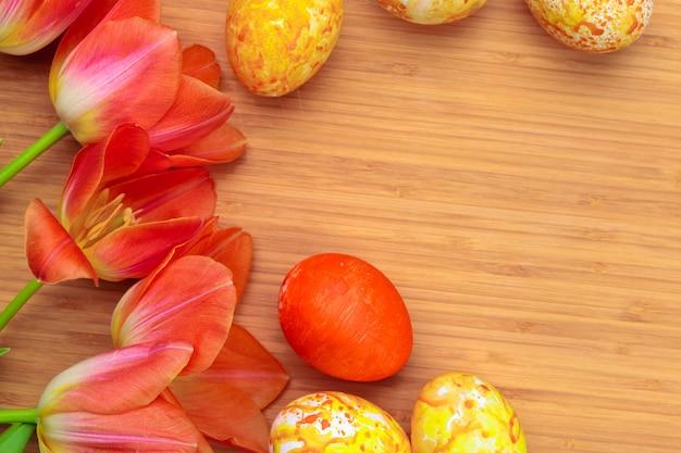 Paaseieren met tulpen op houten raad, pasen-vakantie. copyspace-tekst