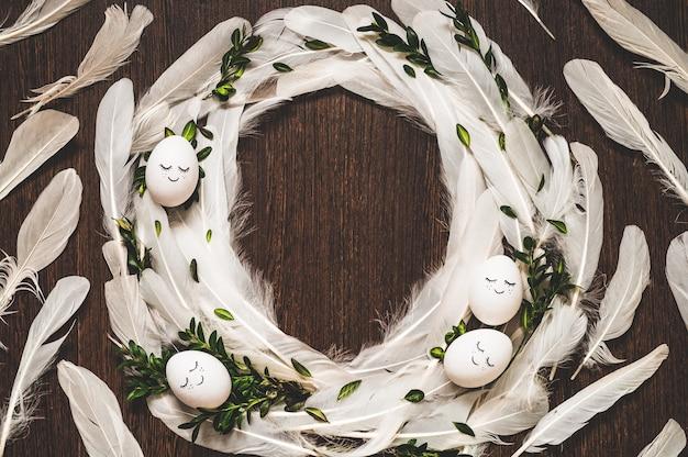 Paaseieren met witte veren op houten tafel
