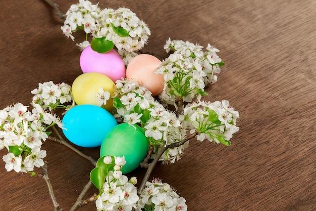Paaseieren op een bloeiende gekleurde eieren lentebloemen