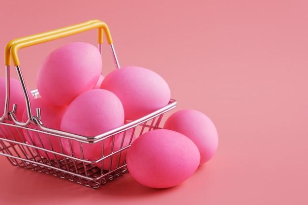 Paaseieren op roze achtergrond en boodschappenwagentje met eierenclose-up.