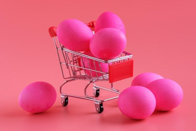 Paaseieren op roze boodschappenwagentje als achtergrond en karretje.