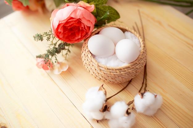 Paaseieren op witte houten lijst. bloemen en snoepjes rondom.