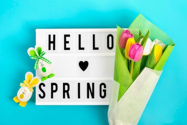 Paaseieren schattig konijntje lightbox met citaat hello-de lente, kleurrijke tulpen op blauwe achtergrond.
