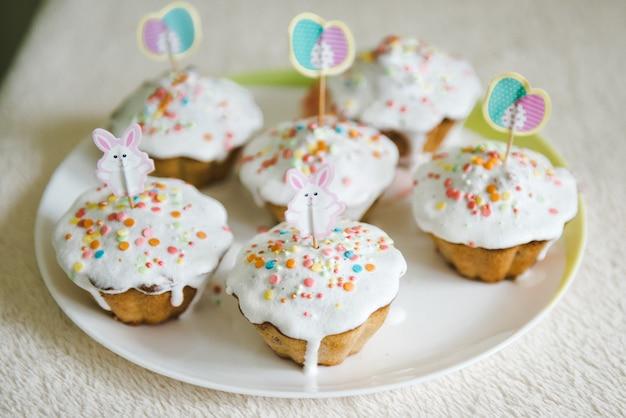 Paashaas cupcakes. pasen-cakes die met room, konijntjesgezicht worden verfraaid.