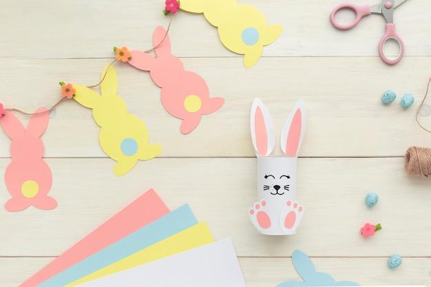 Paashaas decoratie. papier gesneden diy vakantie wit handgemaakte konijn en slinger en kleurrijke konijnen. bovenaanzicht, kopieer ruimte. grappig ronduit.