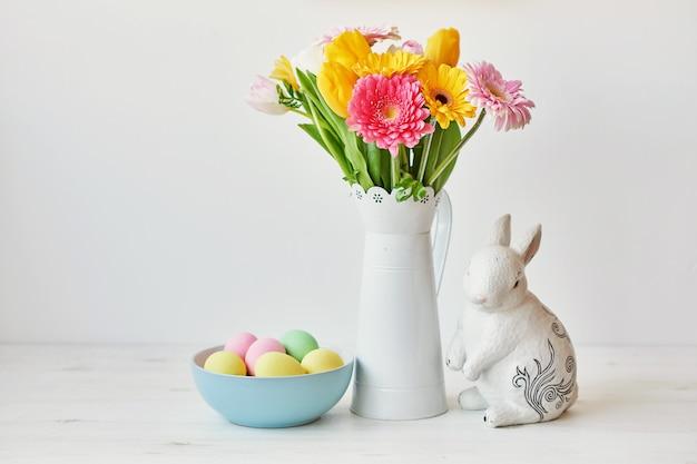 Paashaas en paaseieren op keukenlijst. witte konijnzitting op lijst met boeket van tulpen en rand en kleurrijke eieren. pasen-decoratie met konijn en eieren. pasen kaartsjabloon