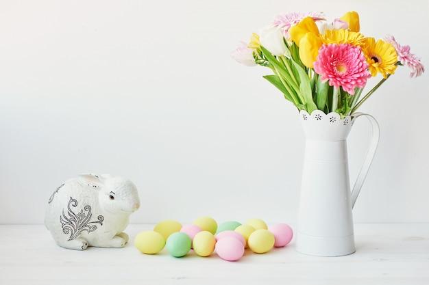 Paashaas en paaseieren op keukenlijst. witte konijnzitting op lijst met boeket van tulpen en rand en kleurrijke eieren.