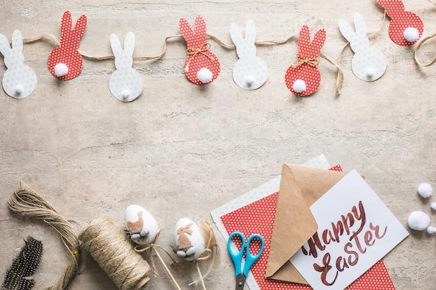 Paashaasdecoratie papier gesneden achtergrond. diy vakantie handwerk slinger van kleurrijke konijnen en knutselgereedschap. bovenaanzicht met kopie ruimte