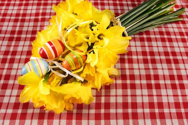 Paaskaart met boeket gele narcissen en handgeschilderde eieren op een tafel met een geruit tafelkleed