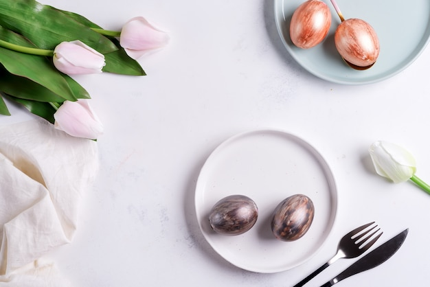 Paaskaart met handgemaakte beschilderde heldere eieren op borden en tulpenbloemen op een lichtgrijze marmeren achtergrond.