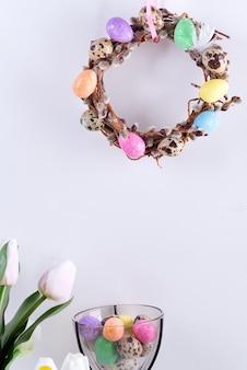 Paaskaart met handgemaakte krans van wilgentakken en geschilderde kleurrijke eieren, tulpenbloemen in vaas tegen lichtgrijze muur.