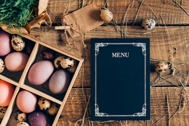 Paasmenu. bovenaanzicht van paaseieren in houten kist en menubord liggend op houten rustieke tafel met hooi
